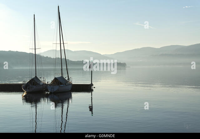 two boats in the harbor on a calm lake and the horizon mists of winter - Stock Image