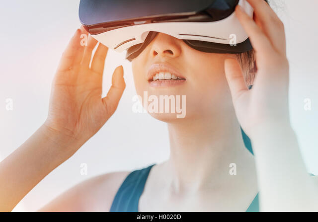Close up shot of asian woman using the virtual reality headset and looking away. Female wearing VR goggles against - Stock Image