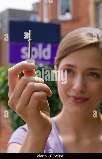Woman first time buyer holds up door key - Stock Image