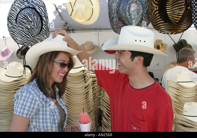 Albuquerque New Mexico State Fair Asians try cowboy hats - Stock Image