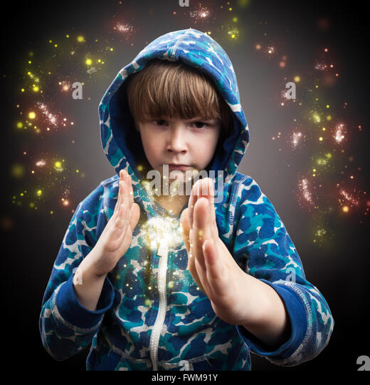 Portrait Of Magician Boy With Sparkles Against Gray Background - Stock Image