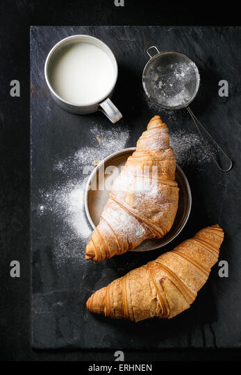 Two fresh baked croissants with sugar powder served with aluminum cup of milk and vintage sieve over black slate - Stock Image