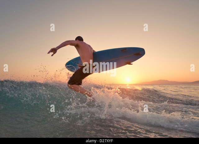 Surfer running into the sea. - Stock Image