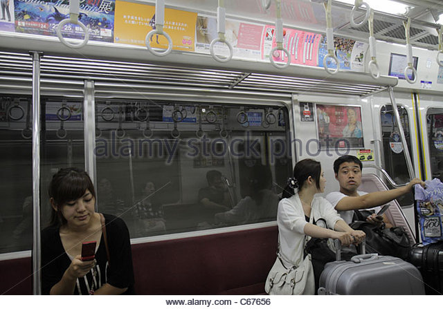 Tokyo Japan Haneda Airport Keikyu Line train Asian woman mobile cell phone man couple luggage riders commuters - Stock Image