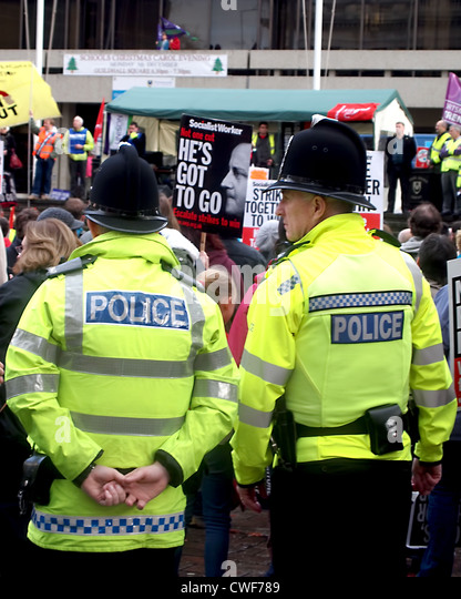 Two police officers watch over a demonstration against government cuts within the public sector at Guildhall square, - Stock Image