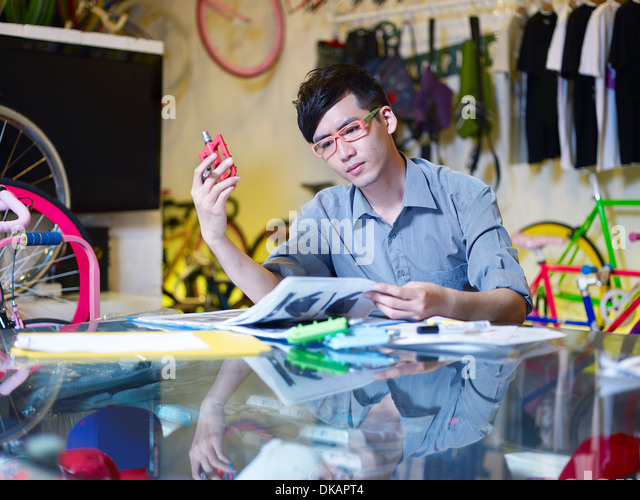 Young man examining bicycle part in bike shop - Stock Image