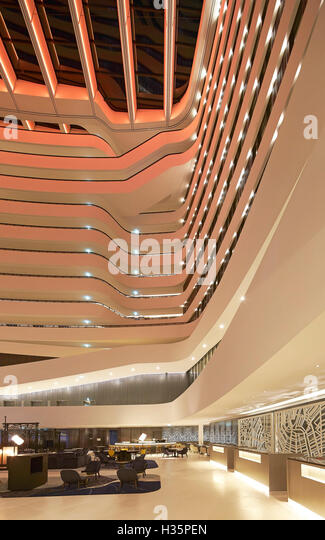 Foyer and reception in full-height atrium. Hilton Amsterdam Airport Schiphol, Amsterdam, Netherlands. Architect: - Stock Image