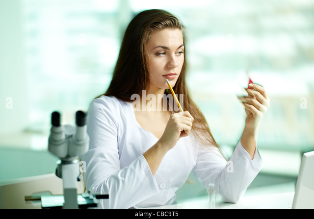 Serious chemist looking at flask with substance - Stock Image