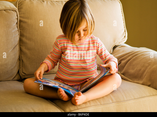 Girl, 3-5 years, sits on a cozy sofa reading a book. - Stock Image