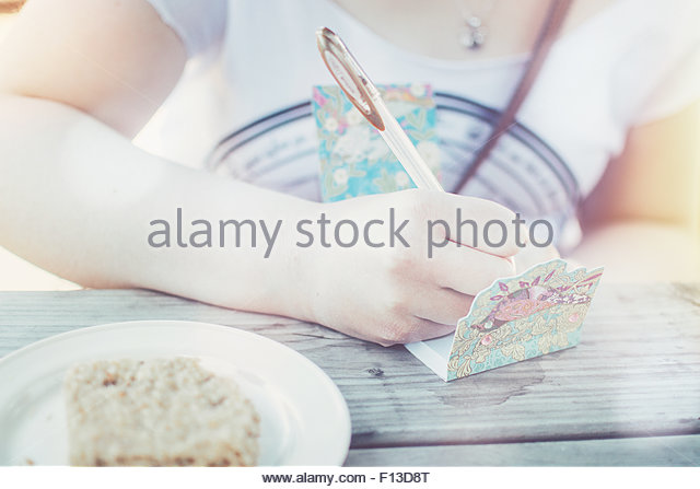 Close-up of a  teenage girl writing in notepad - Stock Image