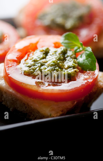 bruschetta with mozzarella, tomato and pesto - Stock Image