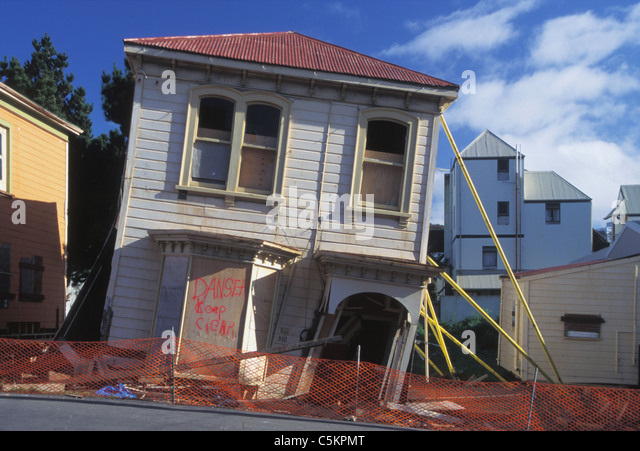 Small damaged timber house, collapsing , propped up to stop it falling over - Stock Image