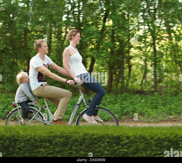 Family with one child riding on bicycle together - Stock-Bilder