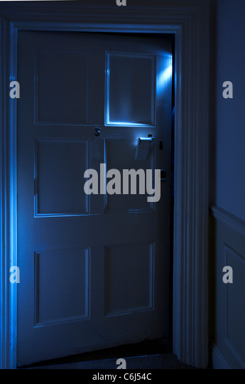 Spooky blue light shining from behind an ajar door - Stock Image