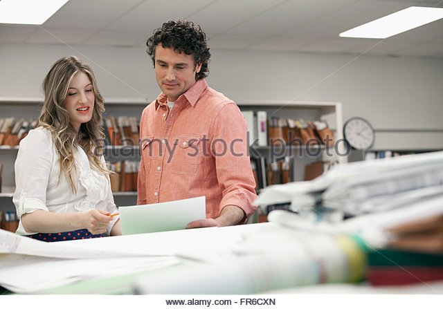 coworkers reviewing plans - Stock Image