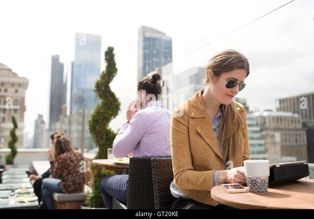 Businesswoman using digital tablet while people working in background - Stock-Bilder