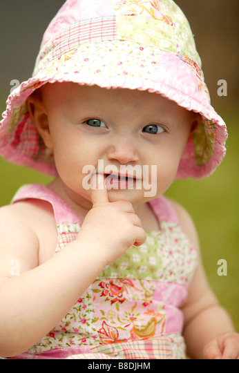 Toddler wearing sunhat with finger in mouth, Saskatchewan, Canada - Stock Image