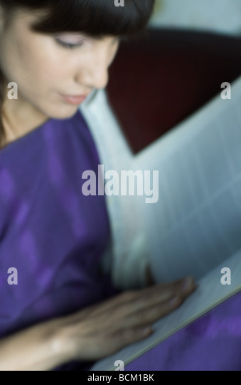 Woman reading book, high angle view, cropped, defocused - Stock-Bilder