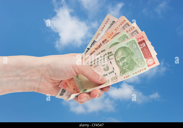 Many diverse Indian rupee bills with the portrait of Mahatma Gandhi are held in the hand. Sky is in the background. - Stock-Bilder