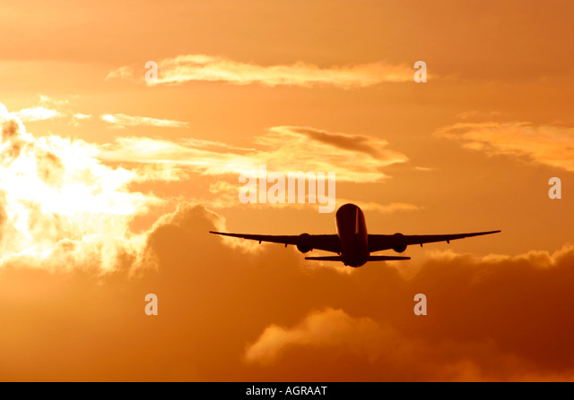 Commercial airplane during flight in clouds and bright sunset - Stock Image