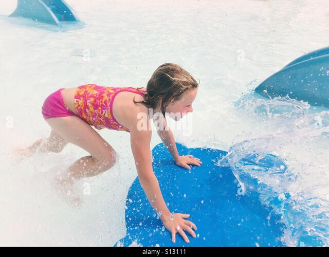 A girl pushes a water toy through an outdoor wading pool creating a splash. - Stock Image