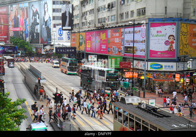 Hong Kong China Island Causeway Bay Yee Wo Street pedestrians crossing bus billboards advertising ads businesses - Stock Image