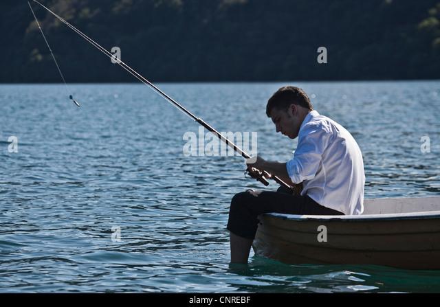 Businessman fishing in rowboat - Stock Image