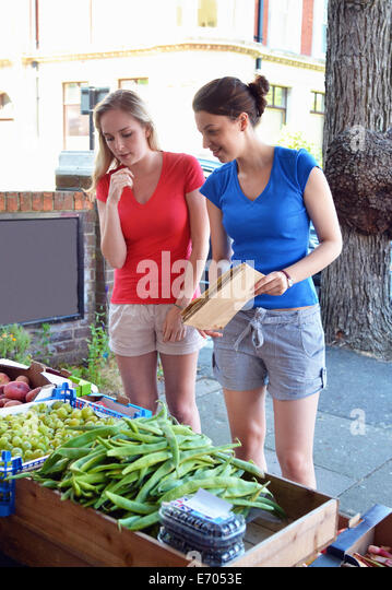 Two young women looking at vegetables at market stall - Stock Image