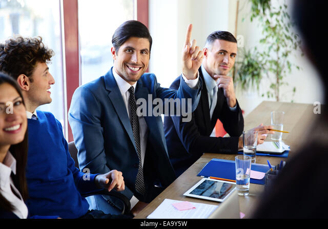 Happy businesspeople sitting at the table in a meeting - Stock Image