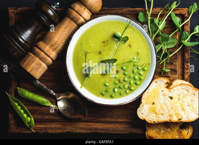 Fresh homemade pea cream soup in bowl with grilled bread - Stock Image