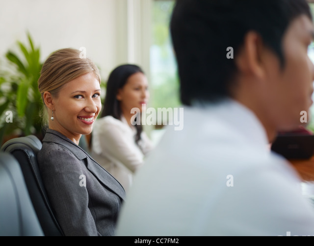 Beautiful young blonde woman working as manager and smiling at camera during business meeting with colleagues. - Stock Image