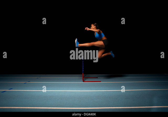Young female athlete jumping hurdle - Stock Image