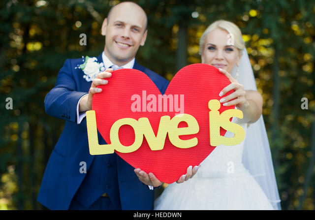 Newlyweds are holding a red heart - Stock Image