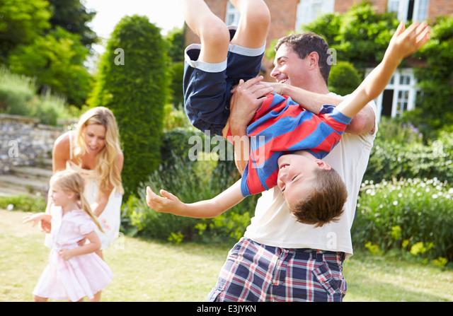 Family Having Fun Playing In Garden - Stock Image
