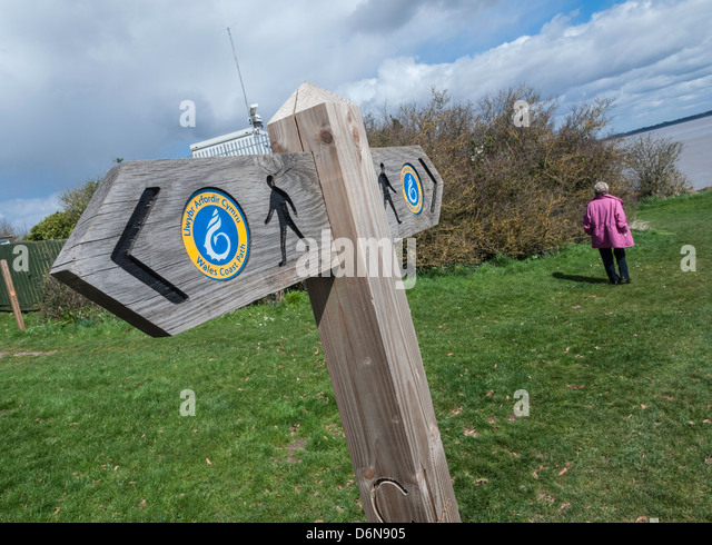 SIGNS ON WALES COAST PATH NEAR BLACK ROCK WITH WALKER IN DISTANCE - Stock Image
