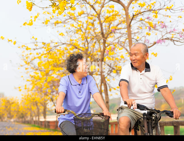 happy asian senior couple ride on bicycle  in the park - Stock Image