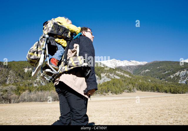 Father hiking with baby in backpack carrier - Stock Image