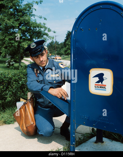 1970s MAILMAN TAKING MAIL OUT OF MAIL DROP BOX - Stock Image