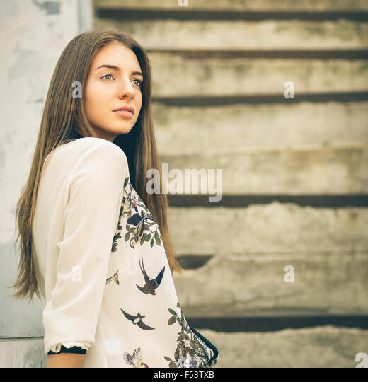 Urban portrait of young hipster girl on stairs with copy space. Pretty girl with long hair looking aside - Stock Image