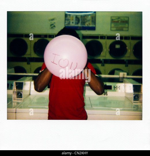 Instant film photograph of man with balloon saying 'I love you' - Stock Image