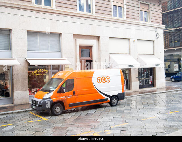 TNT courier van on a winter rainy day in the city center. Italy - Stock Image