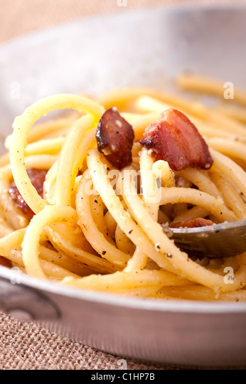 Pasta carbonara - italian dish made of pasta with eggs and bacon - Stock Image