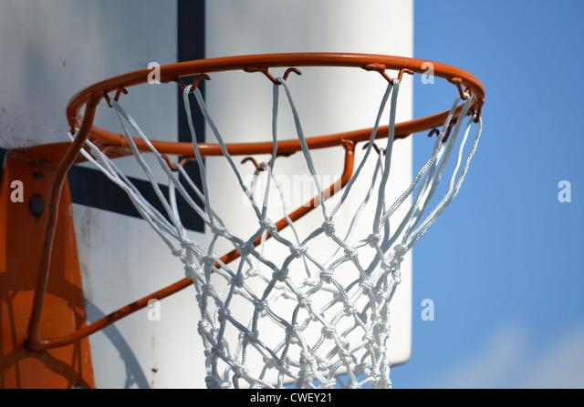 closeup of outdoor basketball hoop with net and backboard - Stock Image