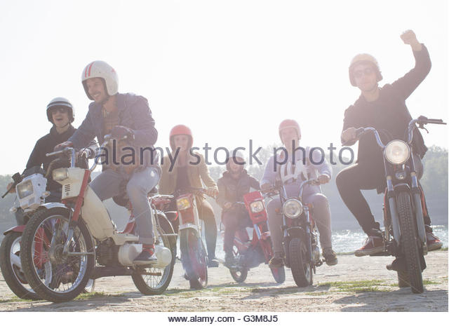 Group of friends riding mopeds along dirt road - Stock Image