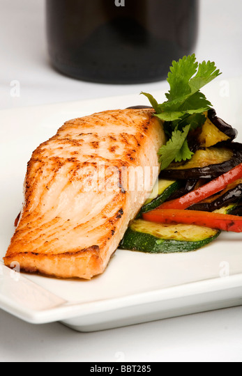 Plate of baked salmon with eggplant and peppers - Stock Image
