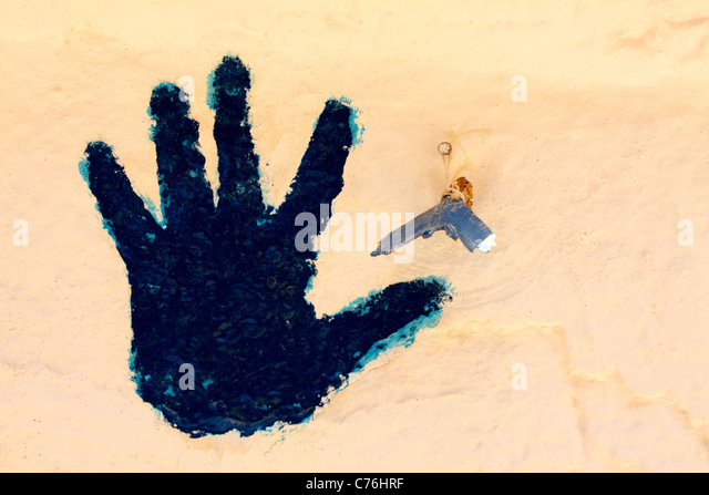 Blue handprint and tail of a fish - a symbol of good luck and prosperity elusive in the Berber people and Tunisians - Stock Image