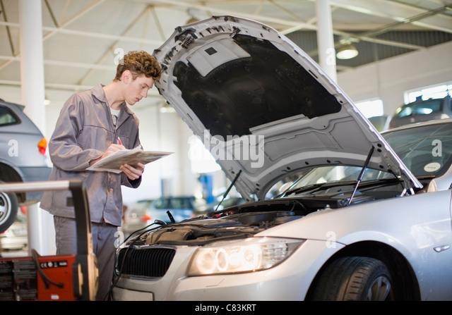 Mechanic examining car engine in garage - Stock Image