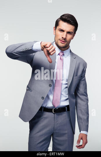 Confident businessman showing thumb down sign over gray background. Looking at camera - Stock Image