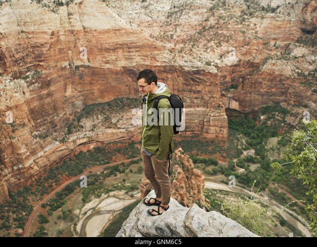 A hiker stands at the top of a peak in Utah's Zion National Park - Stock Image