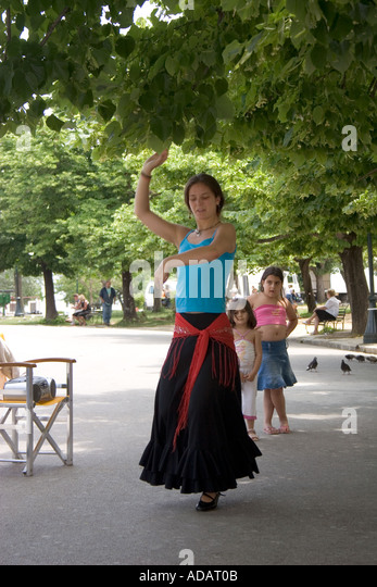 Young Greek woman dances as children look on, Spianada, Kerkyra, Corfu, Greece, Europe, - Stock Image
